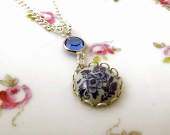 Round ceramic blue Delft  floral necklace with swarovski crystal embelishment hanging from a silver plated chain