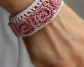 Crocheted white bracelet with pink adornment