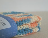 Crocheted Cotton Dishcloths in Peach, Cream, and Blue.