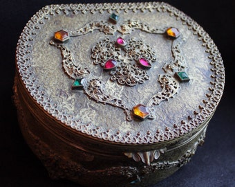 Antique filigree jeweled velvet-lined brass box with four tiny ball feet.