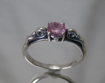 Sterling silver scroll ring with pink cubic zerconia.