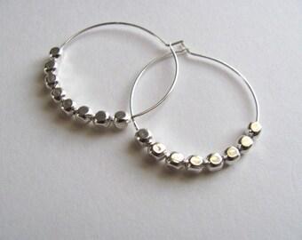Silver hoop earrings with geometric silver beads