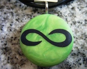 Infinity symbol hand carved on a polymer clay green pearl color background. Pendant comes with a FREE 3mm necklace.