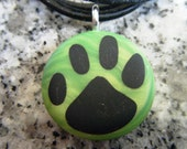 Dog Print hand carved on a polymer clay Green Pearl color background. Pendant comes with a FREE 3mm necklace