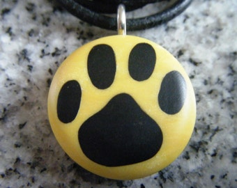 Dog Print hand carved on a polymer clay Yellow Pearl color background. Pendant comes with a FREE necklace