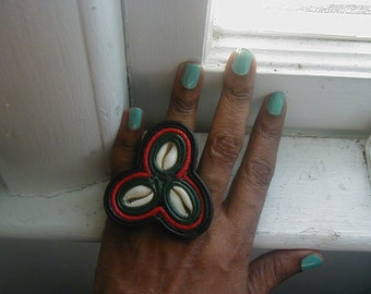 Leather ring, rbg with cowrie shells.