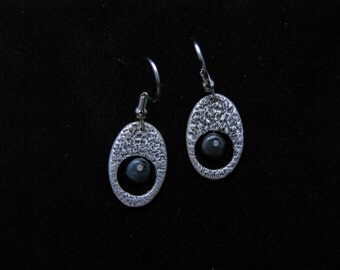 Oval silver earrings with sand paper texture and grey/blue bead