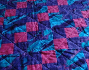 Four patch quilt done in pink, turquoise,and purple.