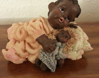 Figurine of Baby Holding Her Doll