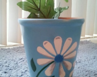 7 inch planter. Hand painted light blue w/ white flowers.