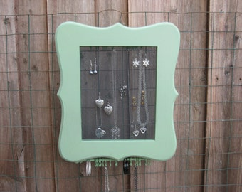 Green vintage look hanging jewelry cabinet for earrings and necklaces.