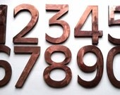 "Large block house number in copper, 1 x 6""/150 mm, polished and mounted on Trespa cladding with sign locator fittings"