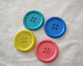 Big plastic buttons, pink, teal, blue and fluorescent. 4 big buttons.
