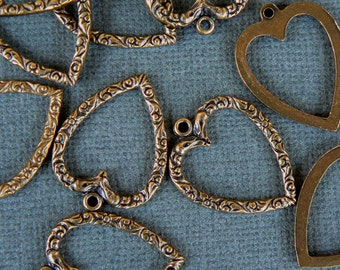 5 pressed metal  Gold Toned Heart Charms. Vintage. One Inch long with a loop.