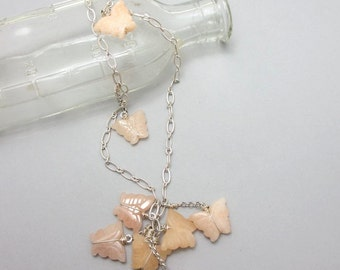Peach Butterflies. Carved quartz butterflies clustered on long adjustable necklace