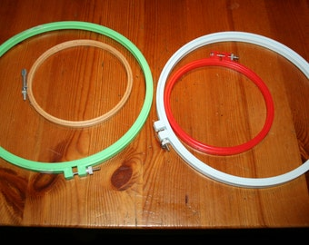 four  vintage embroidery hoops all plastic  one wood different sizes and colors