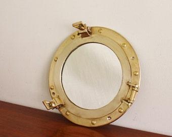 Round brass porthole style mirror