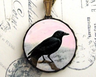 The Lone Crow in Winter Pendant Necklace Antiqued Brass Round Raven Pink Grey