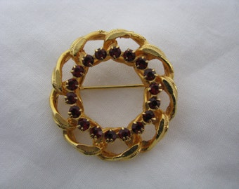 Gold tone vintage circle pin with open border and red rhinestones