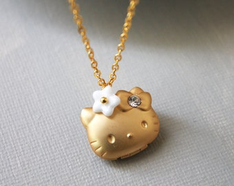 Kitty Locket Necklace. matte gold kitty locket with white flower