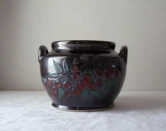 vintage black crock jar with a cherry branch - cookie jar