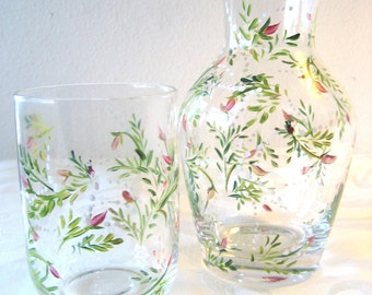 pink rose and baby's breath fern bedside carafe, wineglass, glass carafe has rimmed bottom.