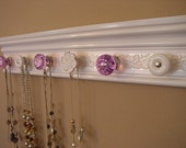 "jewelry/necklace organizer with lavender acrylic  knobs total 7 decorative knobs on  white w/ embossed shimmery background 20 "" long"