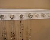 "Jewelry organizer featuring beautiful rhinestone center knob. 9 knobs total on gloss white background 26"" long. wall jewelry storage rack"