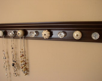 jewelry/ necklace organizer w/ 9 decorative cabinet knobs on brown wood neutral colors 26 inches