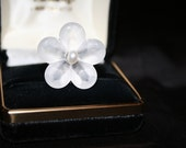 A frosted resin flower with a genuine fresh water pearl center. The pink pearl is a Swarovski Element