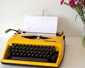 Gorgeous Triumph Tippa Yellow typewriter with black case. 70s Portable