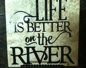 6x6 square tile with Life is better on the river with black vinyl writing