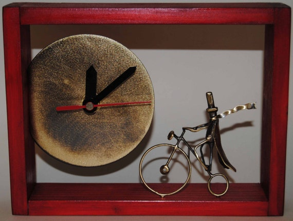 Deep red wooden clock with a brass cyclist.