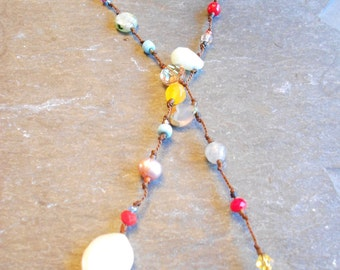 36 inch lariat with semi-precious stones, freshwater pearls, and Swarovski crystals.