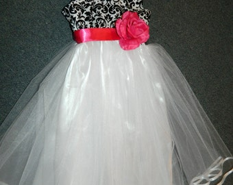 Black and white damask bodice embellished with any color sash/flower attached to billowy white tulle skirt with white satin lining.