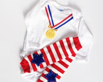 Olympic Baby gold medal one piece with red, white and blue star baby leg warmers