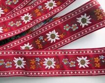 3 yards EDELWEISS & ENZIAN wide Jacquard trim. White, blue, rust, green, on cerise red. 1 1/4 inch wide. 944(3)-B Bavarian dress trim