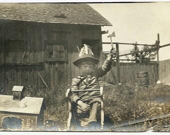 Vintage Snapshot Photo Little Boy In Odd Hat Holds Tomahawk Beside Toy Barn In Farm Yard Photograph