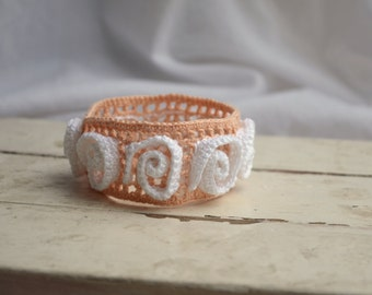 Crocheted peach pink bracelet with white adornment