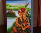 Scottish Cat Greeting Card, Orange Tabby Cat Playing Bagpipes by Eilean Donan Castle