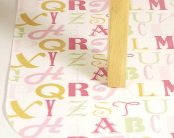 Laminated Cotton Oilcloth Splat Mat  Art cloth kids tablecloth high chair alphabet in pinks and gold SELECT YOUR SIZE