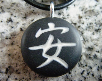Japanese kanji symbol for Peaceful-Safe hand carved on a polymer clay black color background. Pendant comes with a FREE necklace