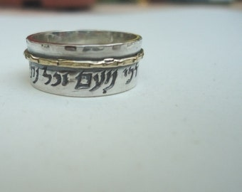 Silver ring with a blessing and a gold hoop around it