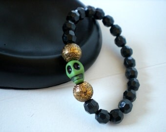 Black bracelet with green skull accent bracelet- elastic- gold accent beads