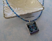 "Necklace - Scrabble tile pendant featuring a butterfly in blue tones, on a beaded necklace - ""Flyaway"""
