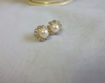 Petite and lovely pierced earrings set with silver tone metal, Faux pearl and shiny rhinestones