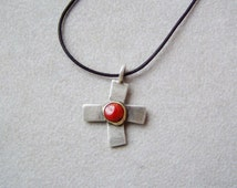 Oxidised stelring cross with 18 K gold and red coral in the mddle, designer slightly crooked modern cross