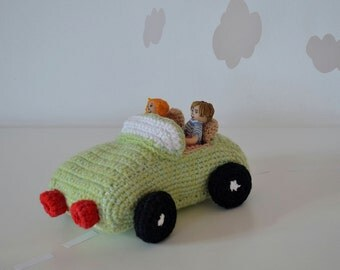 Crocheted green toy cabriolet with passengers, boy and girl handmade from modelling clay