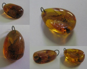 Age old pendant of honey colored amber with expressive inclusions. VINTAGE