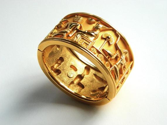Egyptian Elizabeth Taylor Avon wide heavy cuff bracelet hinged designer jewelry golden finish figure hieroglyphics bold statement piece 1993